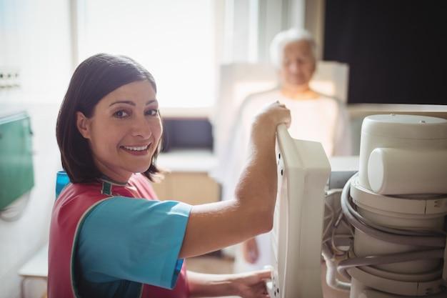 La dottoressa installa la macchina per eseguire una radiografia del torace di un paziente