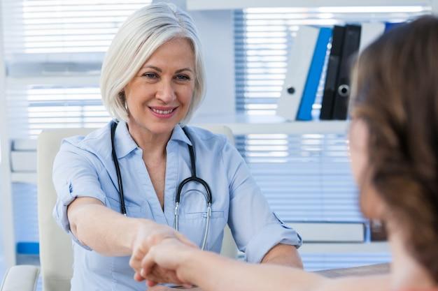 Medico femminile che stringe le mani con il paziente