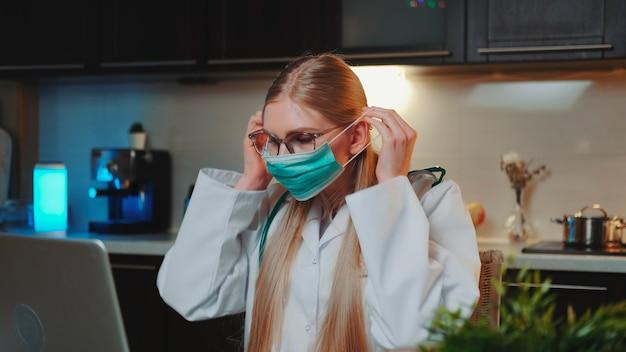 Dottoressa che mostra come indossare la maschera medica tramite videochiamata sul computer che lavora a casa seduta in...