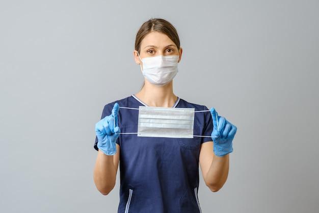 Medico femminile che mostra una maschera medica isolata sopra fondo grigio