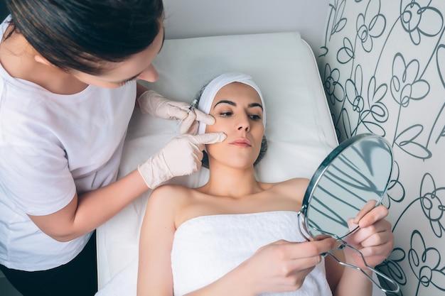 Medico femminile che mostra alla giovane donna graziosa le zone del viso per applicare il trattamento clinico. medicina, sanità e concetto di bellezza.