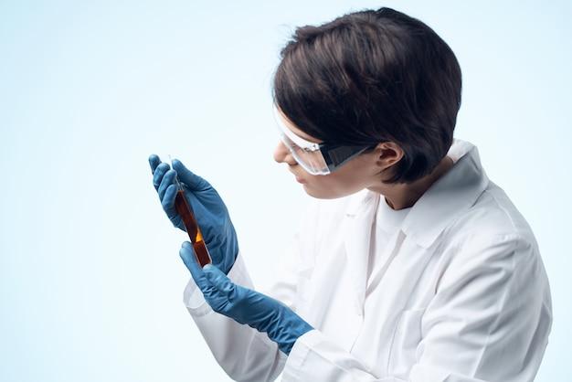 Medico donna seduta al tavolo microscopio ricerca biotecnologia sfondo chiaro