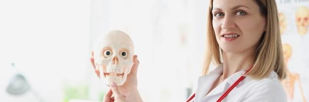 Insegnante di medico femminile che tiene il primo piano del cranio umano