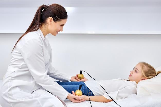 Terapista medico di sesso femminile che tratta il paziente bambino utilizzando uno stimolatore elettrico durante o in fase di trattamento di agopuntura.