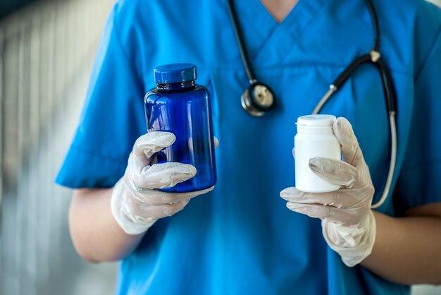 Dottoressa in uniforme che tiene le pillole in clinica
