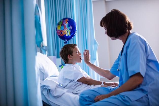 Medico femminile che per mezzo dell'inalatore sul paziente