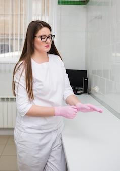 Una dottoressa con gli occhiali e un'uniforme bianca indossa guanti rosa usa e getta in ufficio presso la clinica