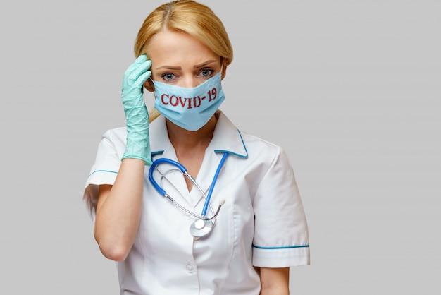 Medico femminile che indossa maschera protettiva e guanti di gomma o in lattice mal di testa e stress