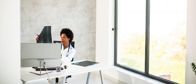 Medico femminile che indossa camice bianco con lo stetoscopio seduto dietro la scrivania in ufficio e guardando l'immagine a raggi x