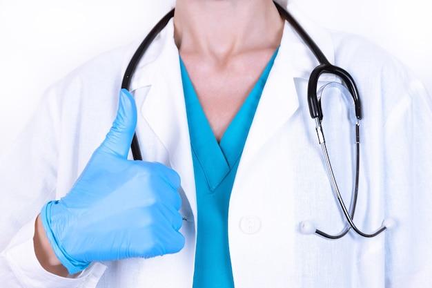 La dottoressa in camice bianco, guanti usa e getta e uno stetoscopio sostiene il pollice