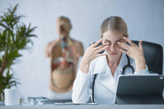 Una dottoressa in camice bianco si siede a un tavolo e massaggia gli occhi stanchi