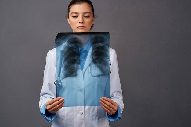 Fondo scuro dell'esame dei raggi x del camice bianco del medico femminile