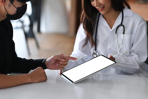 La dottoressa in uniforme medica bianca discute i risultati o i sintomi con il paziente di sesso maschile.
