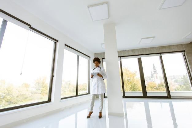 Dottoressa con tavoletta digitale nell'ufficio medico vuoto