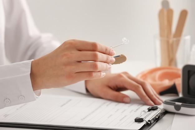 Medico donna con apparecchio acustico al tavolo, primo piano