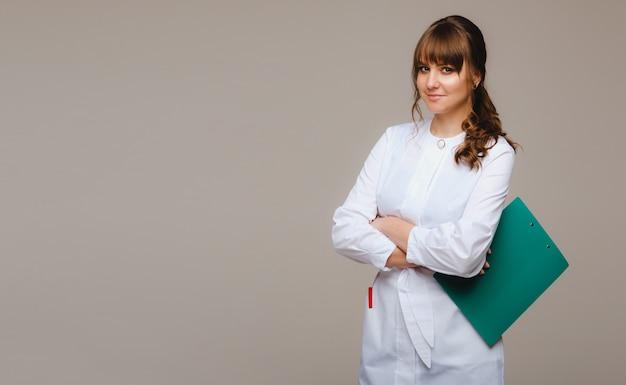 Una dottoressa con un taccuino in mano su un muro grigio