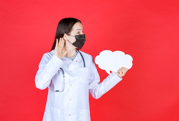 Dottoressa con stetoscopio e maschera nera che tiene un banco informazioni vuoto a forma di nuvola e apre l'orecchio per sentire bene.