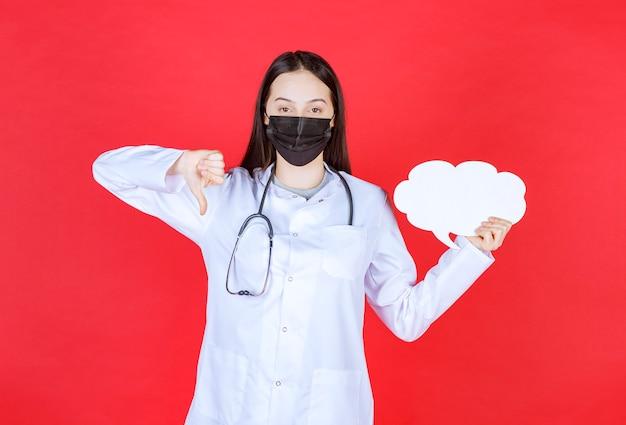 Medico femminile con lo stetoscopio e nella maschera nera che tiene un banco informazioni vuoto a forma di nuvola e che mostra il pollice verso il basso.