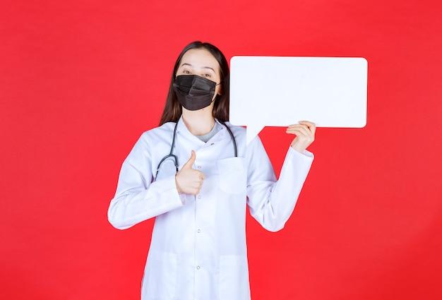 Dottoressa con lo stetoscopio e in maschera nera che tiene un banco informazioni rettangolare e mostra il segno di godimento.