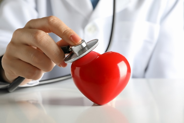 Medico femminile con lo stetoscopio che controlla il battito cardiaco