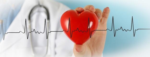 Medico femminile con lo stetoscopio che tiene cuore rosso