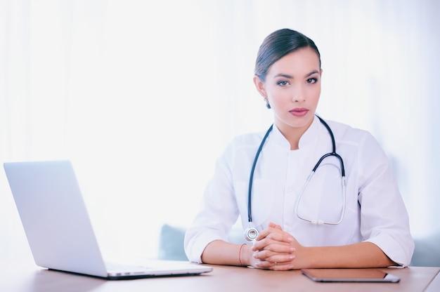 Medico donna con stetoscopio che indossa camice da laboratorio lavora in ospedale e utilizzando laptop