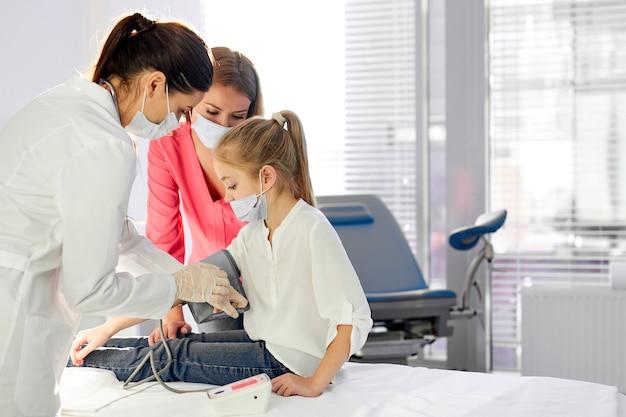 Donna medico femminile che misura la pressione sanguigna della ragazza usando il tonometro, controllando la salute, coronavirus, covid-19, concetto di influenza. nella moderna stanza d'ospedale