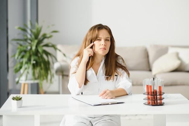 Medico femminile che lavora alla scrivania in ufficio, interno dell'ufficio su priorità bassa