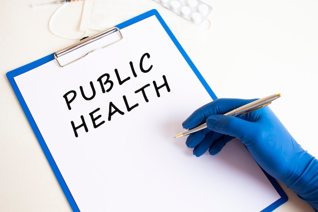 La mano dei medici femminili in un guanto medico fa un'iscrizione salute pubblica