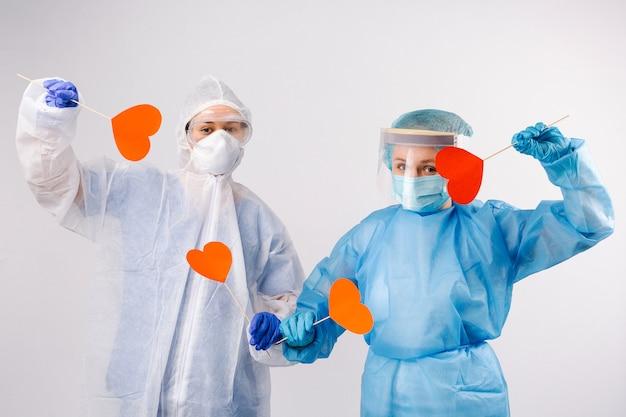 Le dottoresse in equipaggiamento protettivo tengono cuori rossi su sfondo bianco isolato