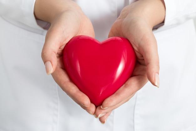 Mani dei medici femminili che tengono e che coprono il cuore rosso. primo piano delle mani del medico. assistenza medica, profilassi o concetto di assicurazione.