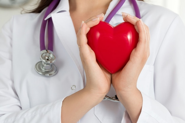 Mani di medici femminili che tengono cuore rosso davanti al petto. primo piano della mano del medico. assistenza medica, profilassi o concetto di assicurazione.