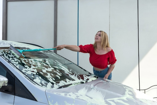 Autista donna che pulisce la sua auto con una spazzola di lavaggio telescopica in schiuma bianca
