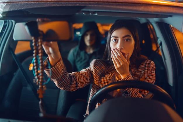 Driver femminile e dirottatore di auto con cappuccio sul sedile posteriore, stile di vita criminale, furto.