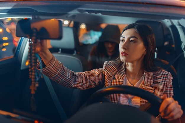 Autista donna e rapinatore di auto con cappuccio sul sedile posteriore, stile di vita criminale, furto.