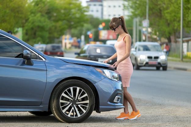 Autista femminile che apre il cofano dell'auto ispezionando il motore rotto su una strada cittadina. concetto di malfunzionamento del veicolo.