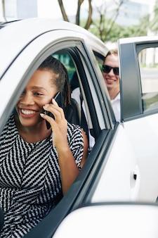 Driver femminile che parla al telefono in una macchina