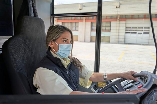 Un'autista donna con maschera facciale che lavora nell'autobus