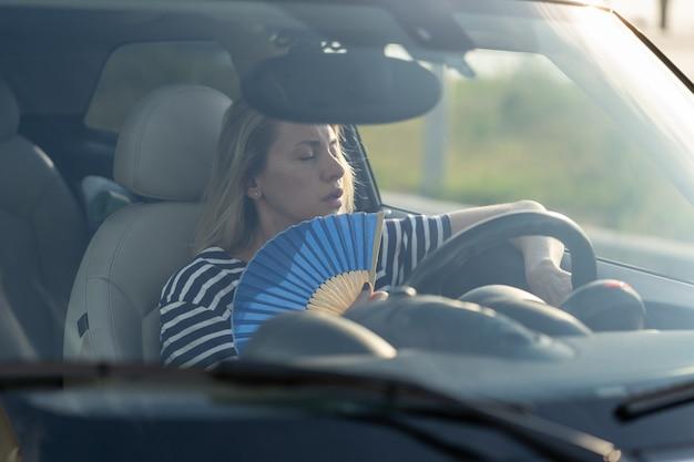 L'autista donna con ventola a mano che soffre di calore in auto ha problemi con il condizionatore d'aria non funzionante