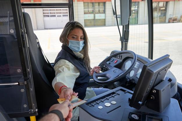 Un'autista donna che lavora per raccogliere le monete nell'autobus