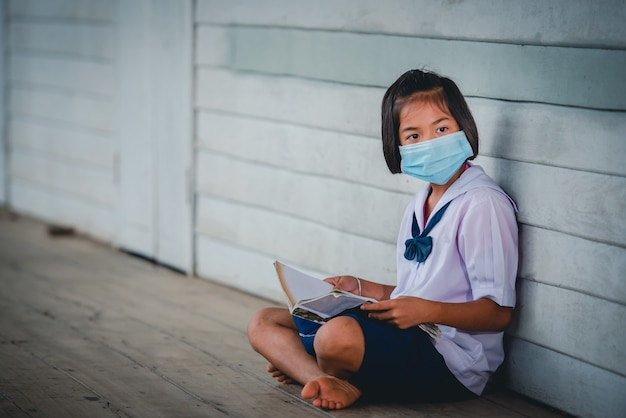 Studentesse asiatiche delle scuole elementari femminili che indossano una mascherina medica per prevenire il coronavirus