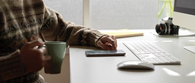 Impiegato femminile che si rilassa con lo smartphone e che tiene una tazza di caffè alla scrivania