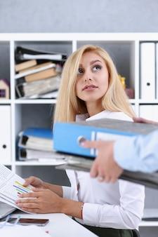 Impiegato femminile mostra pacchetto di documenti da gestire