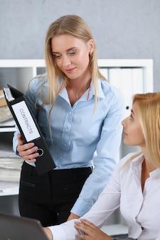 L'impiegato femminile mostra il pacchetto di documenti al manager impegnato
