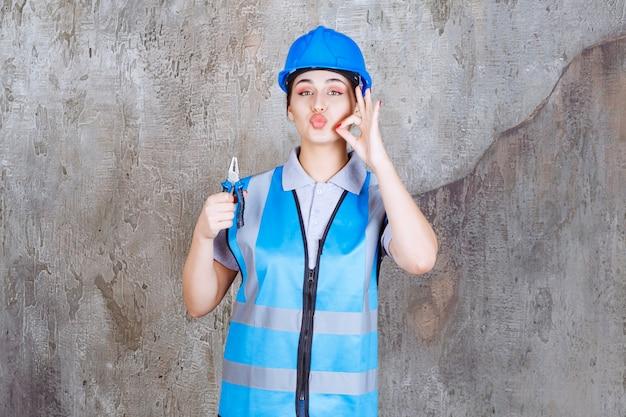 Ingegnere femminile in attrezzatura blu e casco che tiene le pinze per lavori di riparazione e che mostra il segno positivo della mano.