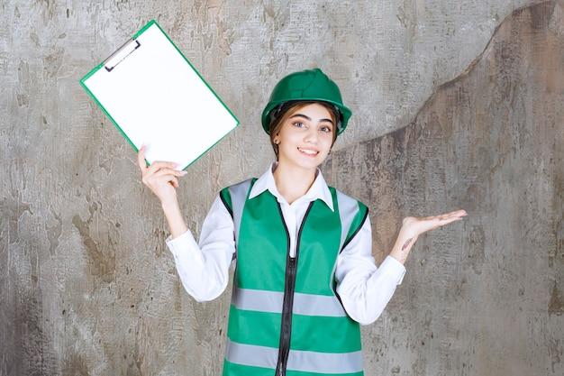 Ingegnere femminile in uniforme verde e casco che dimostra l'elenco dei progetti.