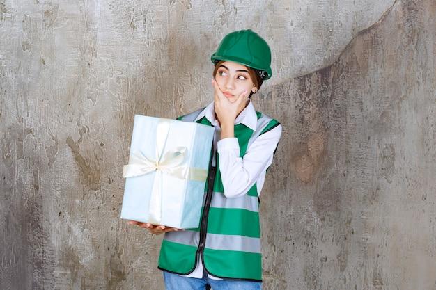 Ingegnere donna in uniforme verde e casco in possesso di una confezione regalo blu e sembra confusa e terrorizzata.