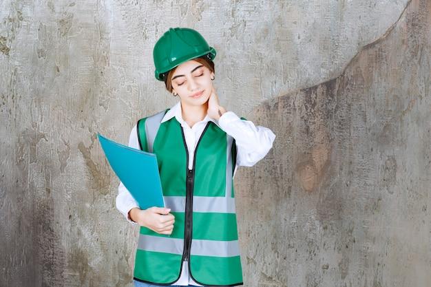 Ingegnere donna in uniforme verde e casco in possesso di una cartella di progetto verde e sembra stanca e assonnata