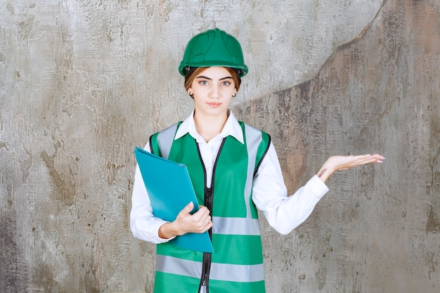 Ingegnere donna in uniforme verde e casco in possesso di una cartella di progetto verde e puntata sul lato destro
