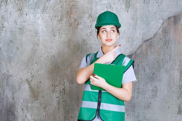 Ingegnere donna in uniforme verde e casco che tiene la cartella del progetto e indica qualcuno